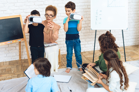 Two little boys get acquainted with technology of virtual reality in classroom. Childrens acquaintance of with high technologies. Stockfoto