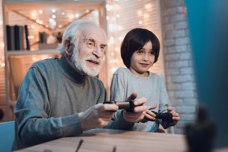Grandfather and grandson are playing video games on computer at table at night at home.