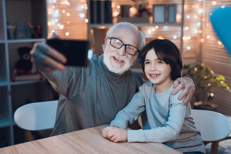 Grandfather and grandson are taking selfie on phone at table at night at home. Stok Fotoğraf - 98228329