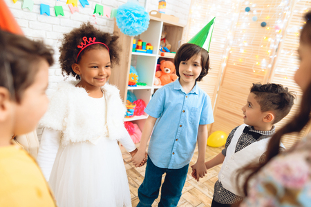 Group of happy children dancing round dance on birthday party. Concept of children's holiday. Happy children have fun on celebration. Stockfoto - 98228354
