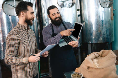 Two bearded men check quality of the malt. Workers of brewery conduct product analysis. Beer crafting. Expertise of beer quality. Quality control Stok Fotoğraf