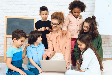 Nice teacher sits with school children who have surrounded her and are looking at laptop. Education of children in elementary school. Elementary School.