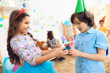 Cute little girl in a hoop-crown gives gift to joyful boy in birthday hat. Gift time. Happy birthday party. Concept of childrens holiday.