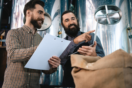 Two men check quality of the malt. Workers of brewery conduct product analysis. Beer crafting. Expertise of beer quality. Quality control Foto de archivo - 98228450