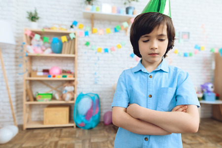 Little boy in festive hat is upset because no one has gone for his birthday. Lonely boy on holiday. Stock Photo