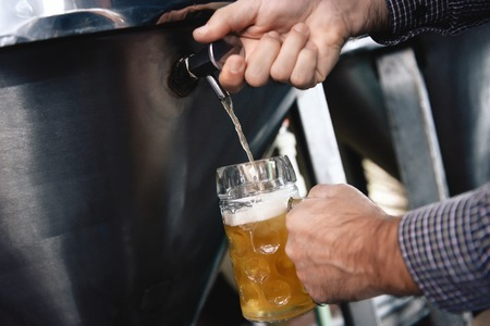 Strong mans hands pour beer in tumbler from beer tap at craft brewery. Brewer pours beer into glass for trial of consignment. Stock Photo
