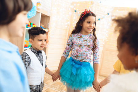 Group of happy children dancing round dance on birthday party. Concept of children's holiday. Happy children have fun on celebration. Stockfoto - 98228501