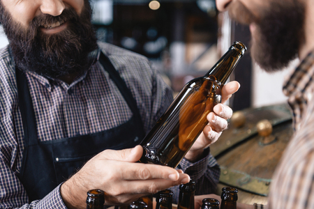 Bearded man holds empty bottle intended for craft beer near brewery. Empty beer bottle. Brewing. Brewery. Beer crafting.