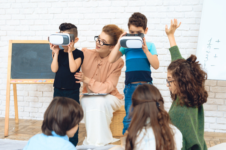 Little schoolchildren get acquainted with technology of virtual reality. Childrens acquaintance of with high technologies. Stock Photo