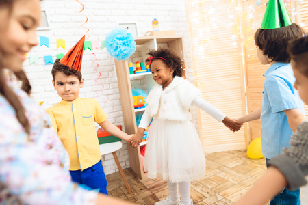 Group of joyful children dancing round dance on birthday party. Concept of childrens holiday. Happy children have fun on celebration.
