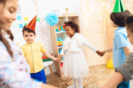 Gruppe frohe Kinder, die runden Tanz auf Geburtstagsfeier tanzen. Konzept des Kinderfeiertags. Glückliche Kinder haben Spaß am Feiern. Standard-Bild - 98229893