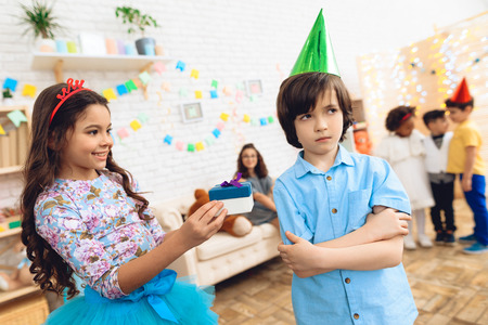 Cute little girl in a hoop-crown gives gift to frustrated boy in birthday hat. Gift time. Happy birthday party. Concept of children's holiday. Archivio Fotografico - 98229939