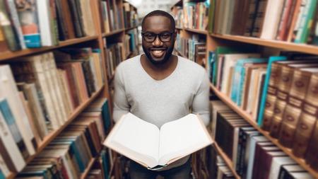 Ethnic African American Guy Reading Book, souriant dans l'allée de la bibliothèque entourée de livres.