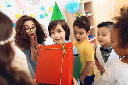 Joyful birthday boy in festive hat receives gift from little girl at birthday party. Happy birthday party. Little children on birthday celebrations.