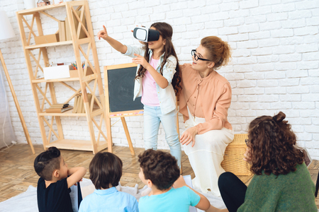 Cute girl looks into virtual reality glasses at classroom of elementary school. School children get acquainted with technology of virtual reality.