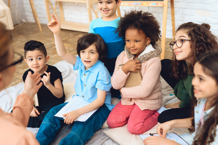 Group of children are pulling hands to answer teachers question in primary school. Education of children in elementary school. Elementary School. Stock Photo