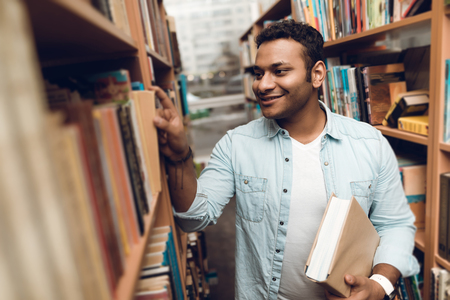 Ethnic indian mixed race student in book aisle of library surrounded by books. Foto de archivo - 98308584