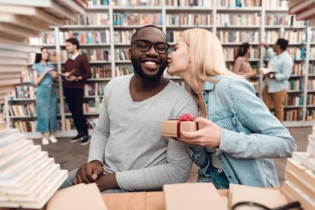図書館の本に囲まれたテーブルに座っているアフリカ系アメリカ人の男と白人の女の子。学生は贈り物をしています。 写真素材