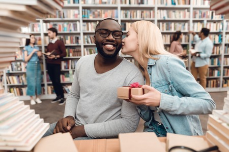 Ethnic african american guy and white girl sitting at table surrounded by books in library. Students are giving gift. Stock Photo