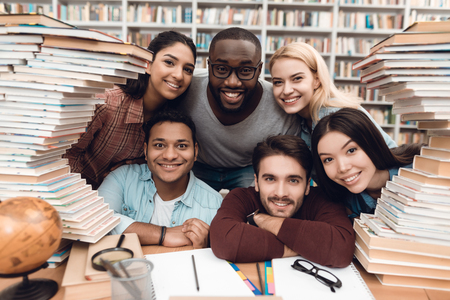 Six ethnic students, mixed race, indian, asian, african american and white sitting at table surrounded with books at library.