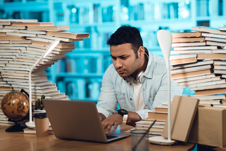 Ethnic indian mixed race guy sitting at table surrounded by books in library. Student is using laptop.