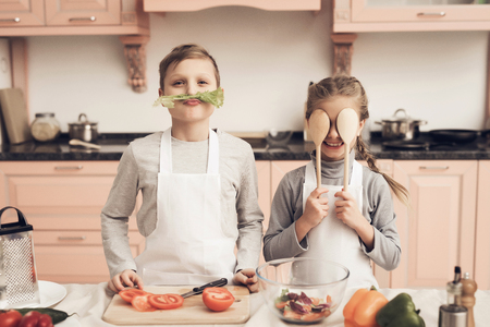 Children at kitchen table in kitchen. Brother and sister are playing with vegetables. Stock Photo