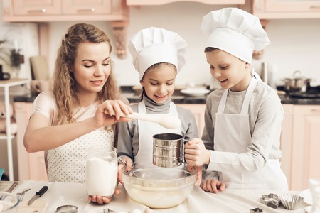 Children in chefs hats with mother in kitchen. Mother is adding flour, brother is sifting it.