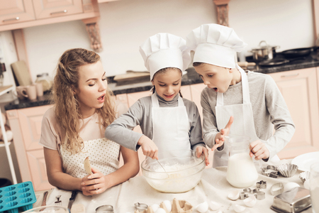 Children in chefs hats with mother in kitchen. Sister is stirring dough and brother is holding milk.