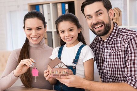Young family is happy to buy new house, holding keys from house and miniature house. Buying a property. Concept of real estate sales. Stok Fotoğraf