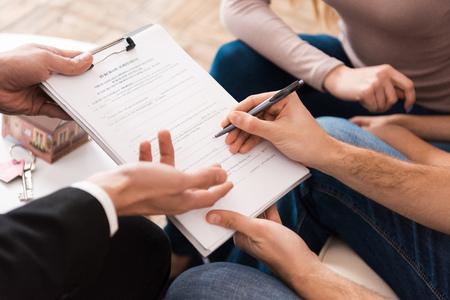 La giovane famiglia firma un accordo commerciale per l'acquisto di una nuova casa insieme a un agente immobiliare. Concetto di vendite immobiliari. Concetto di acquisto di casa. Archivio Fotografico