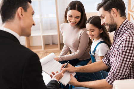 Young family signs business associate agreement to buy house together with realtor. Concept of real estate sales. Concept of house buying. Stock Photo
