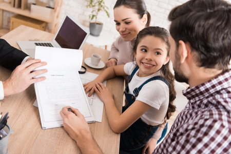 Family man with wife and daughter signs sales contract in office of realtor. Concept of house selling. Confident realtor helps young family sell house. Banque d'images