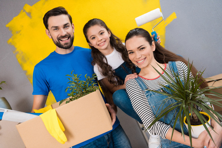 Happy father, mother and little daughter make small renovation in house for putting it on sale. Home repair. Overhaul of house.
