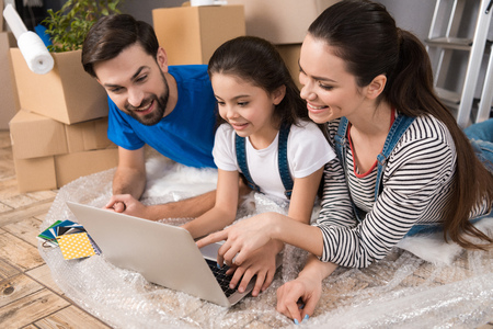 Happy couple with little daughter lying on bubble wrap, looking at laptop screen in repairing house. Home repair. Moving of family to new apartment. Фото со стока