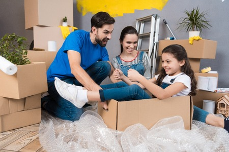 Little girl simulates flight on airplane, sitting in box next to parents. House renovation for sale. Young happy couple with small daughter is doing repairs in new house. Banco de Imagens