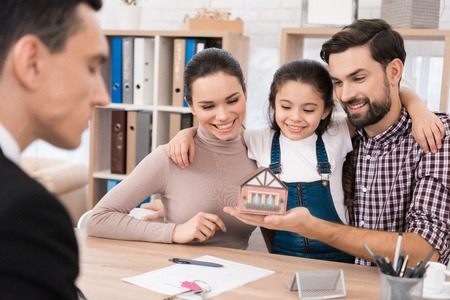 Joyful young family looks at miniature toy house in office of realtor. Confident realtor helps young family buy house. Stock Photo