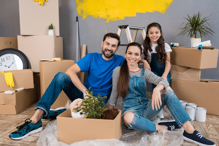 Happy young family dismantles cardboard boxes and makes repairs in new house. Home repair. Family does house repairs together.