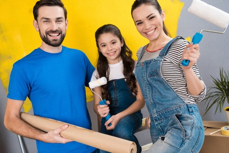 Cheerful father, mother and little daughter make small renovation in house for putting it on sale. Home repair. Overhaul of house.