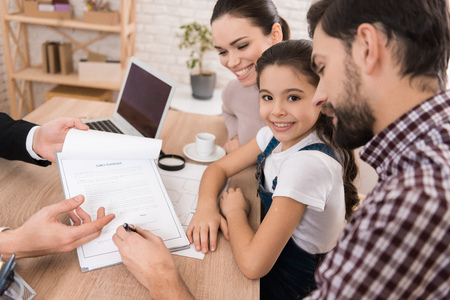 Adult father with wife and daughter signs sales contract in office of realtor. Concept of house selling. Confident realtor helps young family sell house.