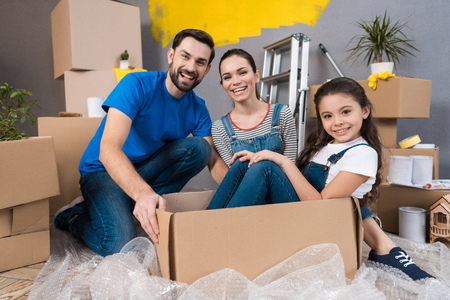 Home repair. Moving young family to new apartment. Repair in house for sale. Happy couple carries small daughter in box at house where repairs are being carried out.