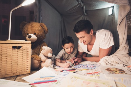 Father and son are drawing with color pencils on paper in blanket fort at night at home.
