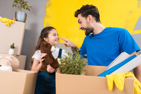 Happy little girl with box of plush toys looks at father which started repair in house. Adult handsome man with little girl, dismantles boxes of things in new house. Standard-Bild - 98363809