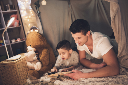 Father and son are reading book with magnifying glass in blanket fort at night at home. Stock Photo