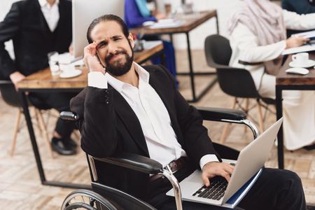 オフィスで働く車椅子のスーツを着た障害者のアラブ人男性。人の頭が痛い。 写真素材