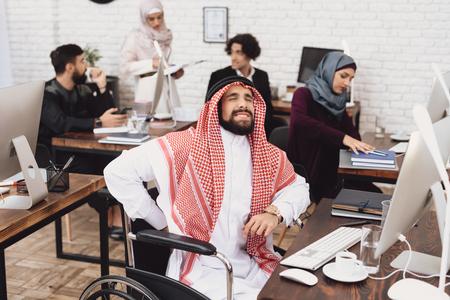 オフィスで働く車椅子で解凍中の障害者アラブ人男性。男の背中が痛い。