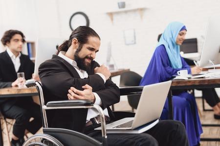 オフィスで働く車椅子のスーツを着た障害者のアラブ人男性。人の肘が痛い。