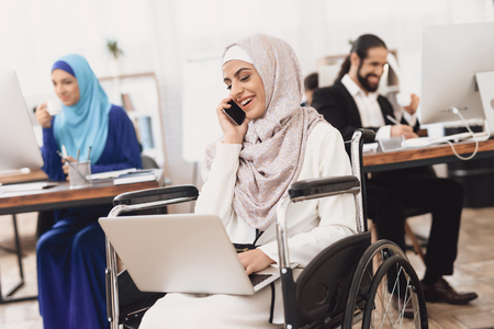 Disabled arab woman in hijab in wheelchair working in office. Woman is working on laptop and talking on phone.