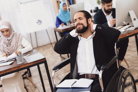 オフィスで働く車椅子のスーツを着た障害者のアラブ人男性。人の首が痛い。