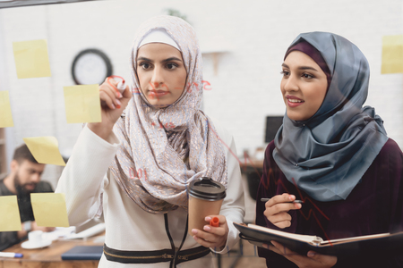 Two arab women in hijab working in office. Coworkers are taking notes on glass board.