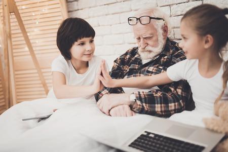 自宅でベッドにいる祖父、孫、孫娘。おじいちゃんが寝ている間、子供たちはラップトップとタブレットを使用しています。